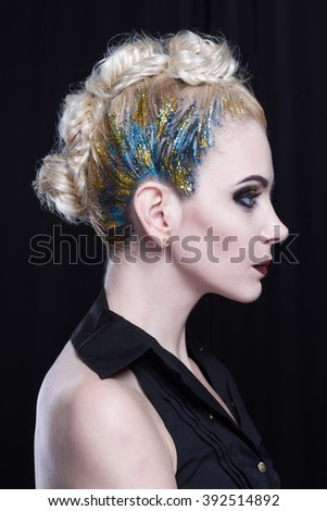 Young attractive blonde woman with creative hairstyle. She is rebellious, she has a colored mohawk with glitter and heavy makeup. Side view. - stock photo