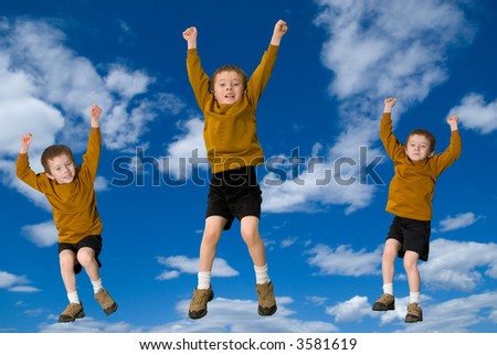 Young attractive boys jumping with a sky background - stock photo