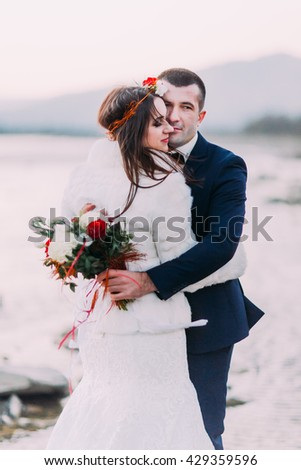 Young attractive bridal couple holding each other on pebble riverside with forest hills as background