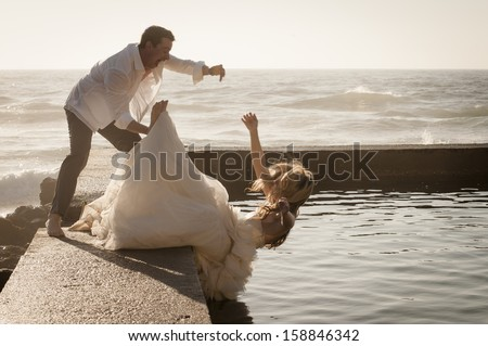 Young attractive bridal wedding couple falling into pool of water - stock photo