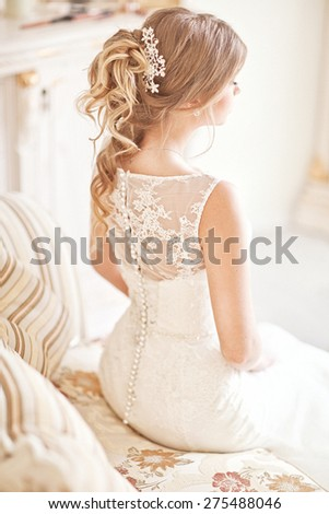 Young attractive bride in ivory tenderness wedding dress posing in interior - stock photo