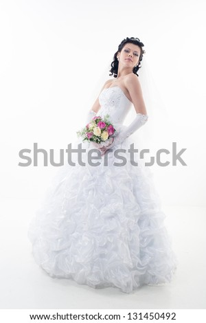 Young attractive bride with the bouquet of white and red roses. Happy bride with a bouquet. Isolated on white background.