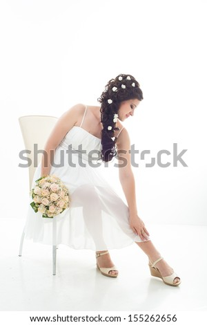 Young attractive bride with the bouquet of white and red roses. Happy bride with a bouquet. Isolated on white background. - stock photo
