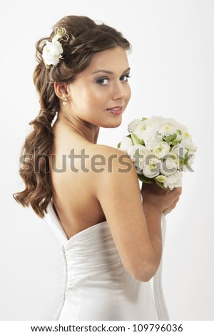 Young attractive bride with the bouquet of white roses - stock photo