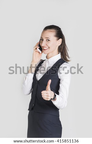 Young attractive brunette business woman giving thumbs up while talking on the phone - stock photo
