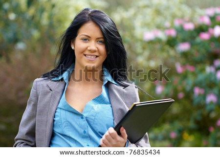 young attractive brunette businesswoman in park, wears blue shirt and grey suit, outdoor shoot