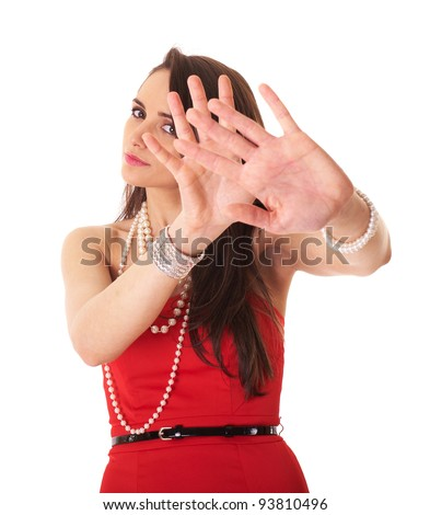 Young attractive brunette in red dress makes stay away, stop gesture using her both hands, studio shoot isolated on white - stock photo