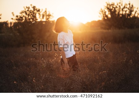 Young attractive brunette standing in the sunset summer field, contemplating