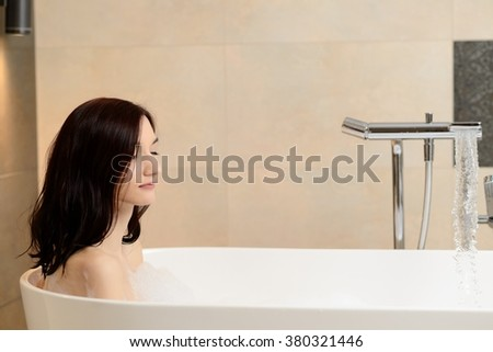 Young attractive brunette taking bath. Relaxed, eyes closed. Woman in bathroom - stock photo
