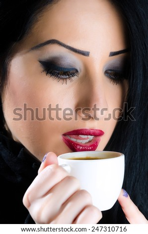 Young, attractive brunette woman holding a coffee cup to her lips - stock photo