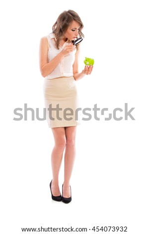 Young attractive brunette woman in a business suit with a piggy bank pig posing in studio isolated on white background.
