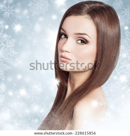 Young attractive brunette woman in a snow. Winter beauty concept. - stock photo