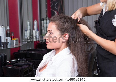 young attractive brunette woman in hairdressing salon - stock photo