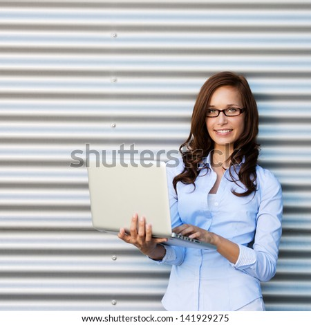 Young attractive brunette woman wearing glasses holding a laptop smiling at the camera.