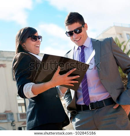 Young attractive Business couple looking at catalogue outdoors. - stock photo