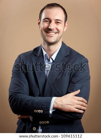 Young attractive business man smiling at the camera. Studio shot - stock photo