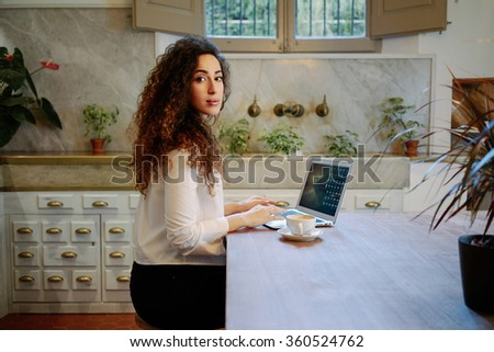 Young attractive business woman checks e-mail on her laptop while sitting in a cafe.Beautiful female freelancer drinking coffee and typing on a keyboard in a coffee-shop - stock photo