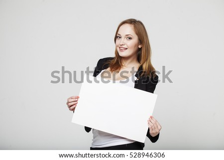 Young attractive business woman in black jacket holding empty shirt of white paper. Studio shoot