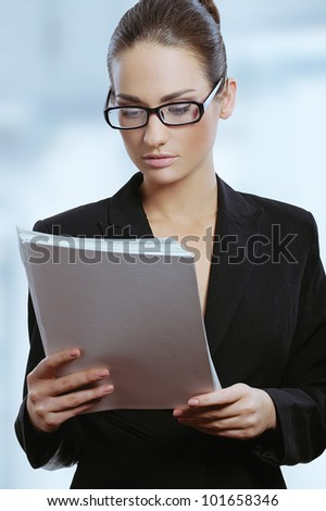 Young attractive business woman in glasses reading contract documents - stock photo