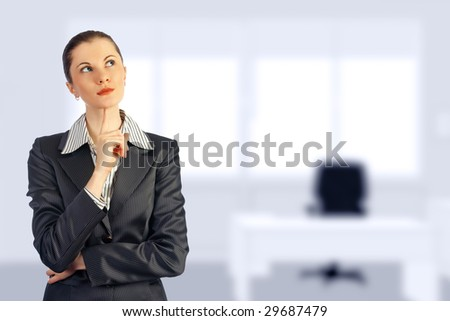 Young attractive business woman in the office (blurred background). Toned in blue. - stock photo