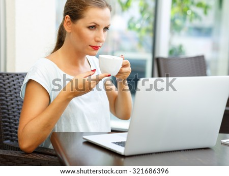 Young attractive business woman sitting in a cafe with a laptop and drinks her morning coffee