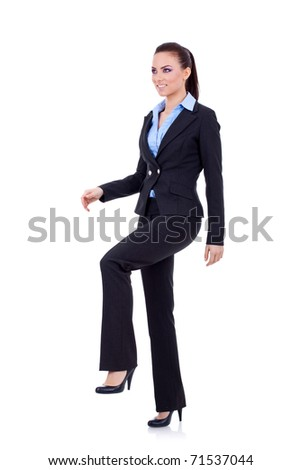 Young attractive business woman stepping on imaginary step - stock photo