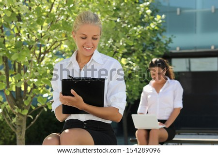 young attractive business women sitting on the street