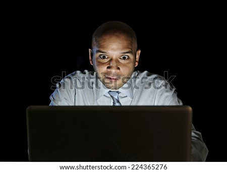 young attractive businessman alone at night sitting at computer laptop watching porn or online gambling isolated on black background on internet chat addiction concept  - stock photo