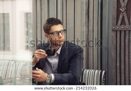 young attractive businessman drinking espresso coffee in the city cafe during lunch time, business concept - stock photo