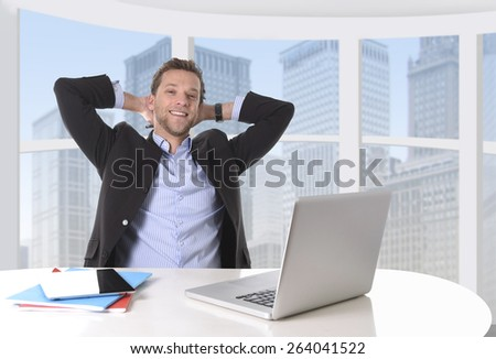 young attractive businessman happy and successful at work at computer desk satisfied and smiling relaxed leaning on chair in front of office window with business district view  - stock photo