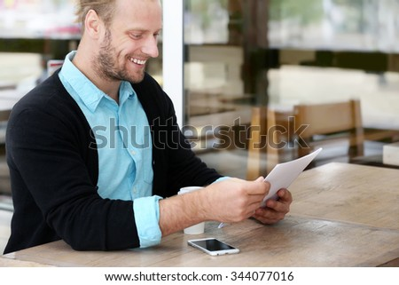 Young attractive businessman having lunch and working in a cafe