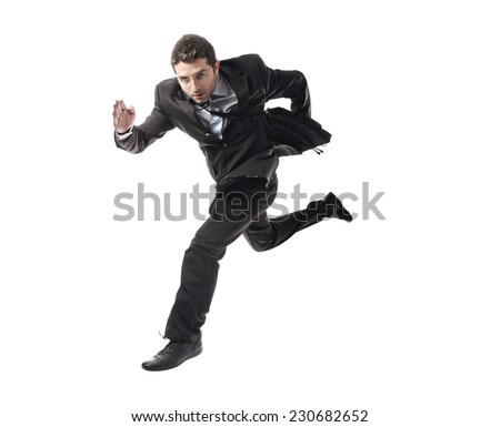 young attractive businessman in athletic pose running late to work wearing suit and tie in stress and overwork or fast success concept isolated on white background - stock photo