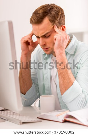 Young attractive businessman in casual clothes having headache while working in office
