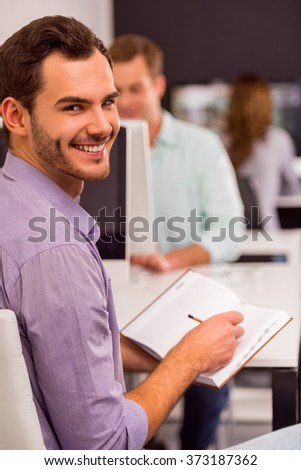 Young attractive businessman in casual clothes making notes, smiling and looking in camera, in the background people working in office