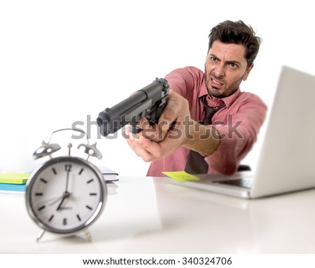 young attractive businessman in stress at office computer desk pointing hand gun to alarm clock in out of time and project deadline expiring concept in angry  and frustrated face expression