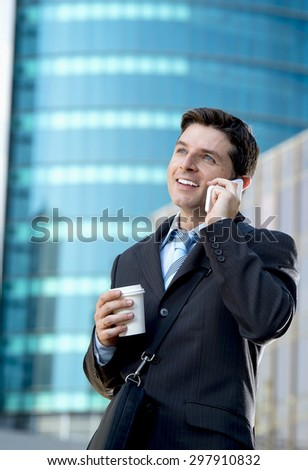 young attractive businessman in suit and necktie talking on mobile smart phone smiling happy and confident standing outdoors in exterior office buildings on business district in success concept - stock photo