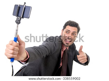 young attractive businessman in suit and tie taking selfie photo with mobile phone camera and stick posing happy and successful isolated on white background - stock photo