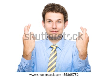 young attractive businessman shows finger crossed gesture, wears blue shirt and yellow necktie, studio shoot isolated on white background - stock photo