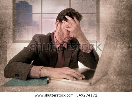 young attractive businessman sitting at office desk working on computer laptop depressed and desperate suffering headache looking frustrated and sad in grunge dirty edition background - stock photo