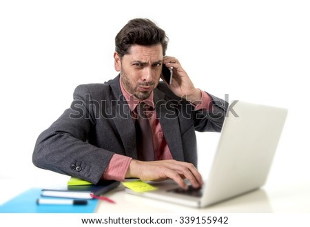 young attractive businessman sitting at office desk working on computer laptop talking on mobile phone overworked looking worried in work stress and  business concept - stock photo