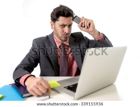 young attractive businessman sitting at office desk working stressed on computer laptop holding mobile phone against his forehead overworked looking worried in work stress and  business concept - stock photo