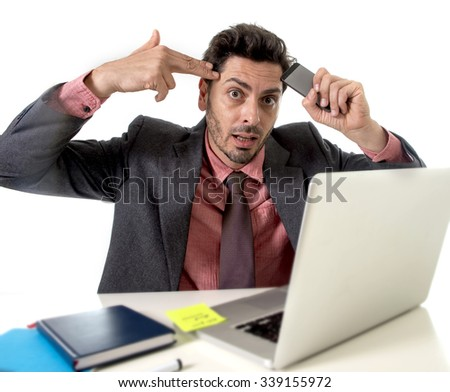 young attractive businessman sitting at office desk working stressed on computer laptop holding mobile phone against his forehead pointing hand in gun sign to his tempo overworked in work stress  - stock photo