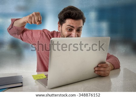 young attractive businessman sitting at office desk working stressed on computer laptop overworked throwing punch in work stress frustration and business mess concept - stock photo