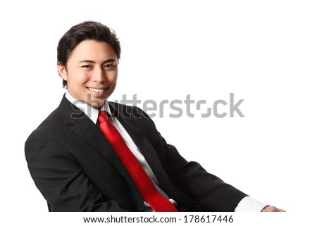 Young attractive businessman sitting down wearing a black suit with red tie. White background.