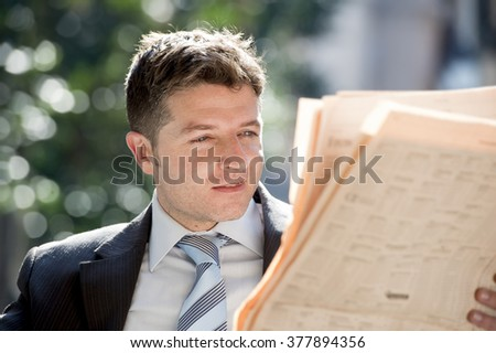 young attractive businessman sitting outdoors for breakfast pause early morning reading news in newspaper relaxed and concentrated in information media and business people concept