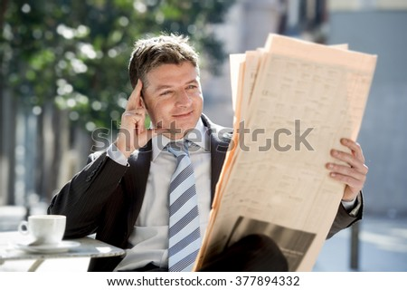 young attractive businessman sitting outdoors for breakfast pause morning reading news in newspaper relaxed and smiling happy in information media and  business people concept