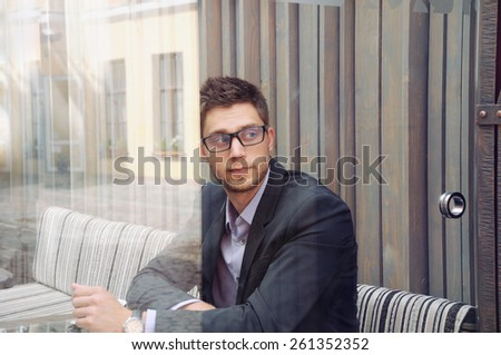 young attractive businessman using device and drinking espresso coffee in the city cafe during lunch time, business concept - stock photo