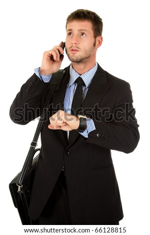 Young attractive businessman with briefcase and talking by phone, impatient checking the time. Looking forward to go. Studio shot. White background. - stock photo