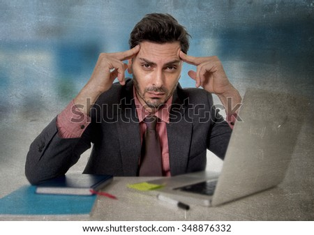 young attractive businessman working on computer laptop at office desperate and worried suffering headache in work stress and business problems concept grunge edit - stock photo