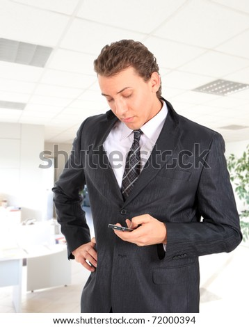 Young attractive businessman writing a text message in an office environment.
